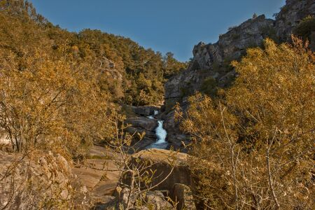 waterfall between rocks and trees with a blue sky Stok Fotoğraf - 132613915