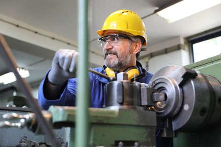 Man operating lathe grinding machine