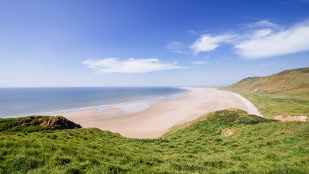 Rhossili bay sandy beach on a sunny cloudy day summer time green vegetation in south wales
