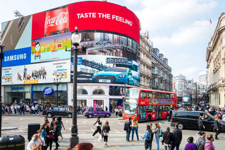 Piccadilly Circus in London busy traffic London red bus people and old screen daytime