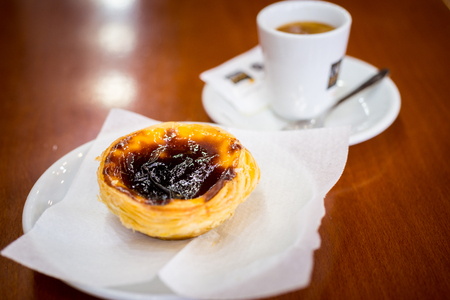 Portuguese Egg Tart and Coffee on brown wooden table in a local Pastelaria