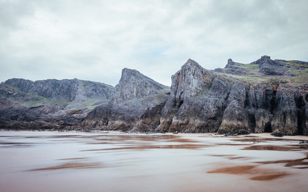 Rocky Sea Shore On A Cloudy Day In Rhossili, Wales Coast Path Stock Photo