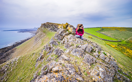 Female Backpacker Looking Into Distance From A Cliff At Rocky Sea Shore On A Cloudy Day In Rhossili, Wales Coast Path Stock Photo