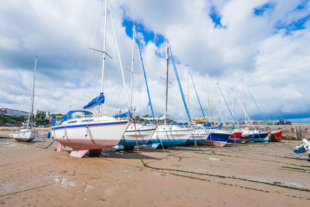 Boats in the bay at low tide in Tenby bay, Wales Stock Photo