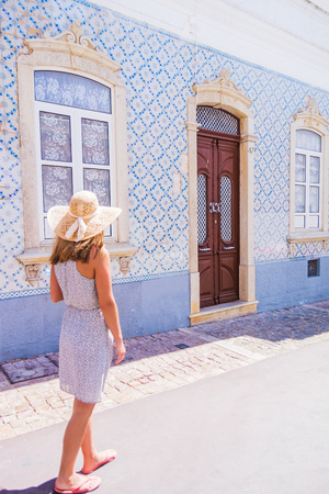 Woman wearing a hat, walking on the streets of Albufeira. Traditional tiles - azulejos covered house on the street. Algarve, Portugal Banco de Imagens