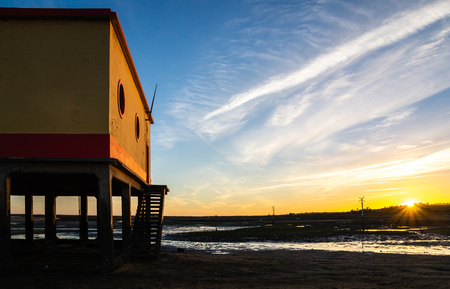Sunset beach view of the historical life-guard building in Fuseta, Ria Formosa Natural park, Portugal Stock Photo