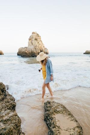 Turista en busca de modelo femenino caminando por la playa Barranco das Canas, cerca de Portimao, Portugal.