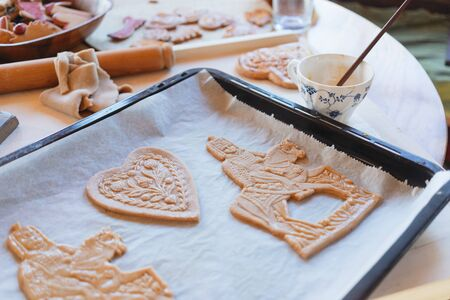 Tradittional home-made gingerbread baking. Egg brushing the ginger dough cut-outs. Budapest, Hungary Stock Photo