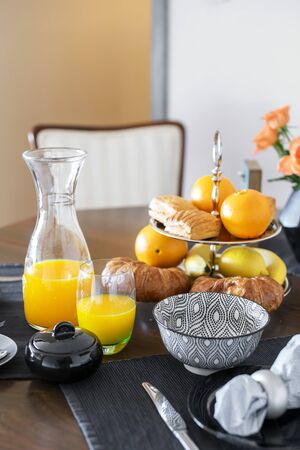 Close shot of continental style breakfast with freshly baked puff pastry and squeezed orange juice served on a dark hardwood dining table. 版權商用圖片