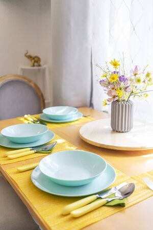 Colorful set of tableware and a bouquet of wild flowers on a brown wooden dining table in natural light, angled view. 版權商用圖片