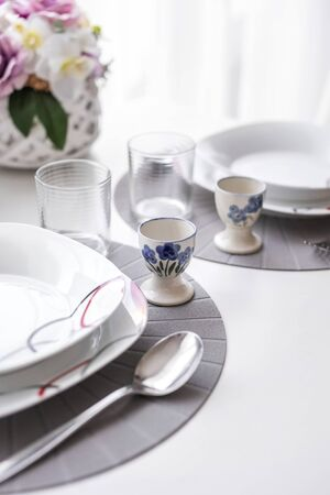 Minimalist white tableware on a white surface dining table in natural light, angled view.