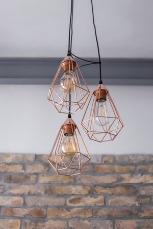 Set of three rose gold light fixtures in front of a white and brick wall background.