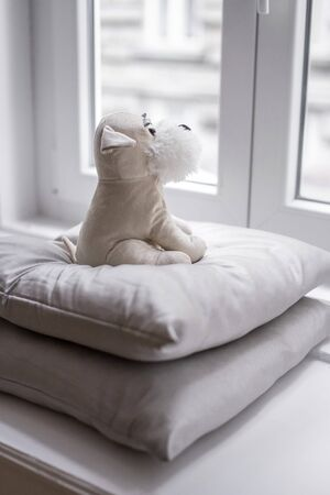 Beige plush puppy sitting on pillows, looking out the window.