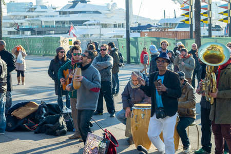 Barcelona, Spain - February 8, 2015: Street musicians playing music and people on streets enjoying it on a sunny mediterranean winter day.