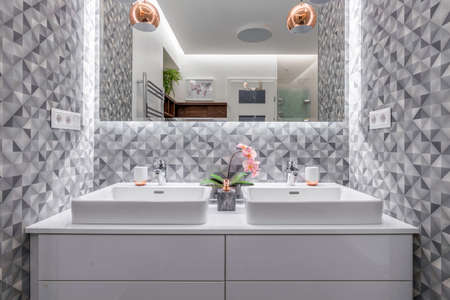 Budapest, Hungary - April 18, 2019: Double sink in a luxurious white marble bathroom in an Airbnb accommodation, straight view.