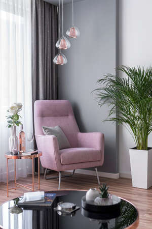 Budapest, Hungary - April 18, 2019: Luxurious reading corner with a grey wall, decorated with rose gold coffee table and hanging fixtures. 新聞圖片