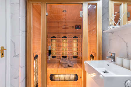 Budapest, Hungary - April 19, 2018: Home sauna inside a white luxurious marble bathroom in an Airbnb accommodation. 新聞圖片