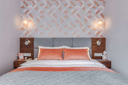 Budapest, Hungary - April 18, 2019: Luxurious bedroom with modern stylish rose gold wallpaper, coral pillows and wooden grey headboard.