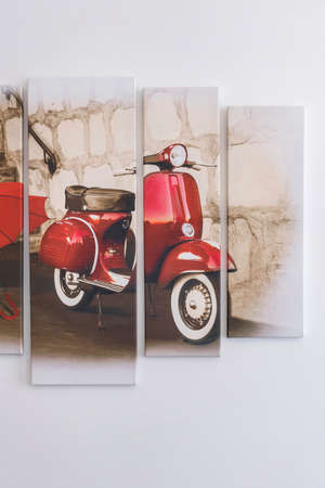 Budapest, Hungary - April 1, 2019: Picture of red Vespa hanging on a white wall.