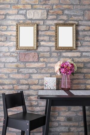 Two identical picture frame mockups hanging on the brick wall above the breakfast table.