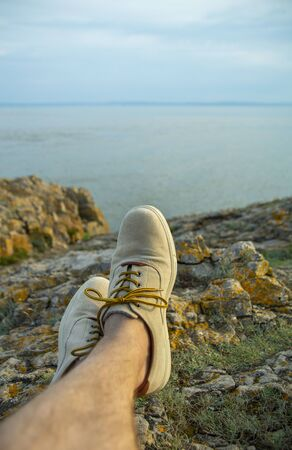 Feet of male tourist resting on the rocks at the beach at sunset, looking at the water.