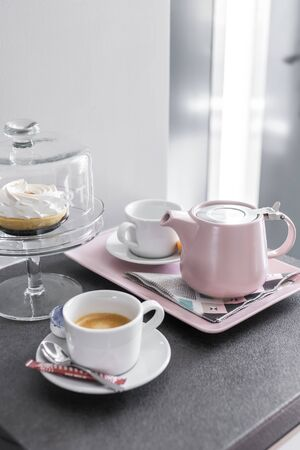 Coffee pot and cups setup on a tray and dessert cake in bright light mood - still life.