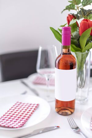 Mockup of a standing rose wine bottle on a dining table in natural daylight.