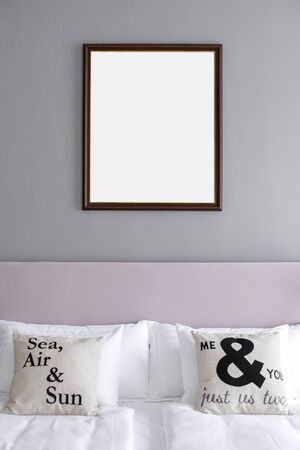 Picture frame mockup hanging on the wall above the bed in a grey and rose theme minimalist bedroom. 版權商用圖片