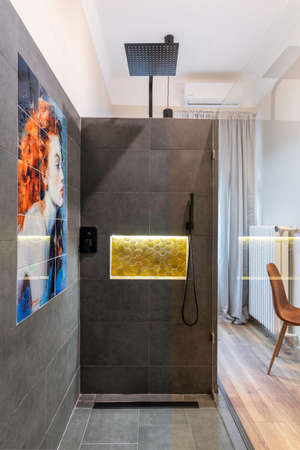 Budapest, Hungary - February 16, 2020: Glass shower with grey granite stone tiles and female painting, inside the room. 新聞圖片