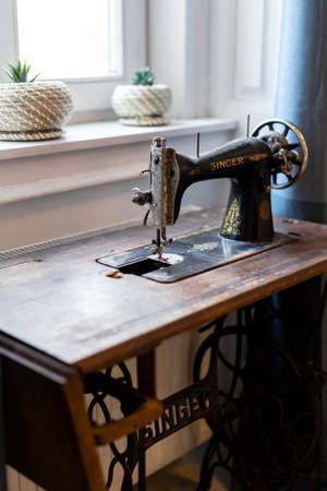 Budapest, Hungary - October 3, 2019: Vintage Singer sewing machine in front of the window - still life, home decor. 新聞圖片