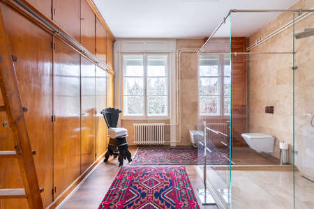 Budapest, Hungary - January 30, 2020: Bathroom with modern glass shower, antique furniture and rugs on the floor.