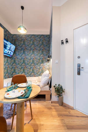 Budapest, Hungary - February 16, 2020: Entry hall of a modern tiny home space with dining area and sleeping corner. 新聞圖片