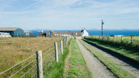 Martin's Haven, Wales - July 1, 2017: Dirt road leading to West Hook Farm Camping with St. Brides Bay in the background - Pembrokeshire West Wales UK.