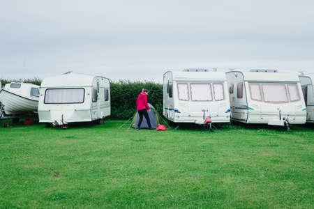 Martin's Haven, Wales - June 30, 2017: Woman pitching a tent between caravans at West Hook Farm Camping on a cloudy day in Pembrokeshire, Wales UK.