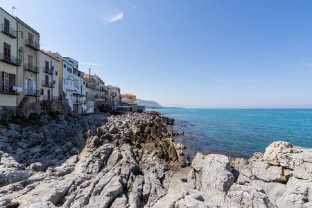 View over the coastline and residential buildings from Bastione di Capo Marchiafava bastion lookout point on a sunny day in Cefalu - Sicily, Italy.