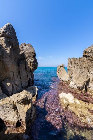 Idyllic view over the turquoise sea from the rocky coastline on a sunny day in Cefalu - Sicily, Italy.