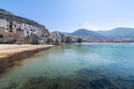 Idyllic view of turquoise sea and houses with Rocca di Cefalu rocky mountain in the background seen from historical old port of Cefalu - Sicily, Italy 版權商用圖片