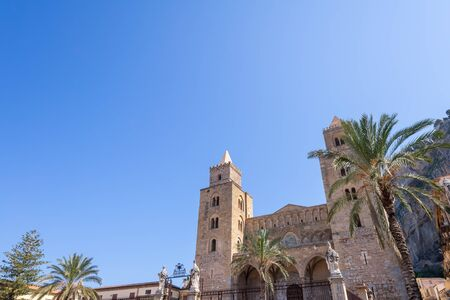 The towers of Duomo di Cefalù Cathedral with clear blue sky and copy space in Cefalu Sicily Italy from an angled view.