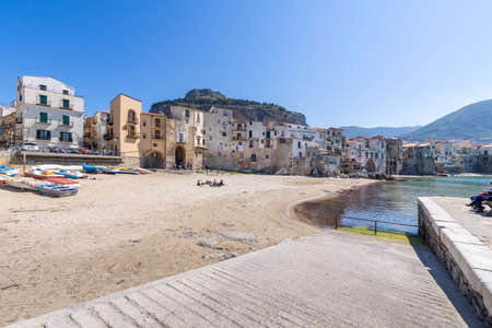 Cefalu, Italy - March 24, 2019: Turquoise sea and residential buildings with Rocca di Cefalu rocky mountain in the background on a sunny day in Sicily