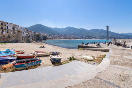 Cefalu, Italy - March 24, 2019: View over the town with mountains in the background, seen from the old port on a sunny day in spring.