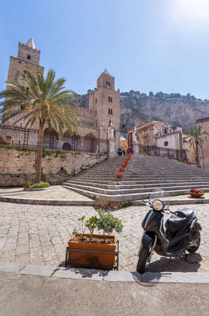 Cefalu, Italy - March 24, 2019: Few people around Duomo di Cefalù with Rocca di Cefalù in the background in Sicily - copy space, angled view.