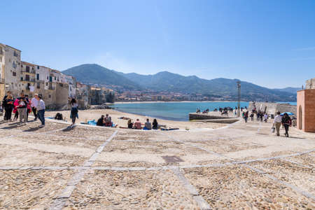 Cefalu, Italy - March 24, 2019: Historical old port busy with people walking and relaxing on the beach on a sunny day in spring.