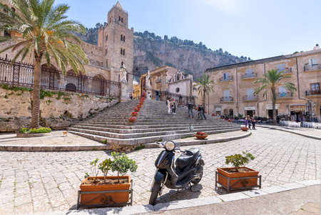 Cefalu, Italy - March 24, 2019: People walking around Duomo di Cefalù with Rocca di Cefalù in the background in Sicily on a sunny day - angled view. 新聞圖片