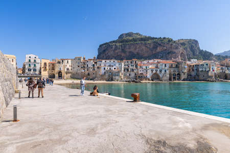 Cefalu, Italy - March 24, 2019: People walking in the historical old port, looking over to Rocca di Cefalu rocky mountain in Sicily on a sunny day.