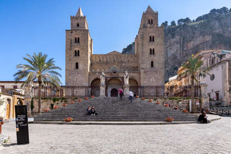 Cefalu, Italy - March 24, 2019: Few people at Duomo di Cefalù Cathedral with Rocca di Cefalù in the background in Sicily on a sunny day - front view.