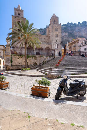 Cefalu, Italy - March 24, 2019: Few people around Duomo di Cefalù with Rocca di Cefalù in the background in Sicily on a sunny day - angled view. 新聞圖片