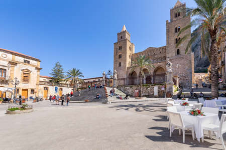 Cefalu, Italy - March 24, 2019: People walking on the street around Duomo di Cefalù in Sicily on a sunny day in spring - angled view. 新聞圖片