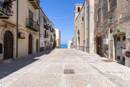 Cefalu, Italy - March 24, 2019: Empty walkway leading to Bastione di Capo Marchiafava bastion lookout point with a peek over the sea.