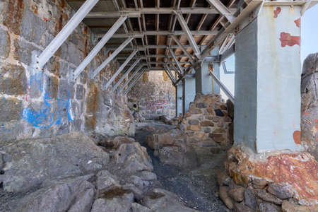 Cefalu, Italy - March 24, 2019: Empty passage and metallic building structure under the houses built on rocks on the coast.