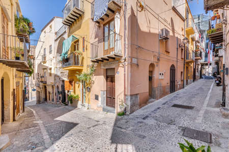 Cefalu, Italy - March 24, 2019: Colorful view of empty streets corner with residential buildings on a sunny day in Sicily.